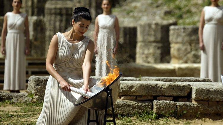 L'actrice grecque Thali Prokopiou allume la flamme olympique, le 25 mars 2004, juste avant les JO d'été organisés à Athènes (Grèce).  (ARIS MESSINIS / AFP)