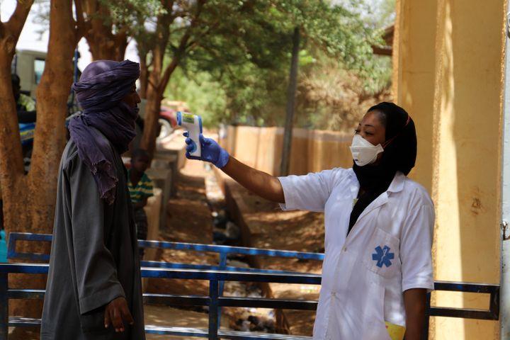 Une infirmière prend la température d'un homme dans le cadre de la campagne contre le coronavirus à Gao au Mali, le 26 mars 2020. (SOULEYMANE AG ANARA / AFP)