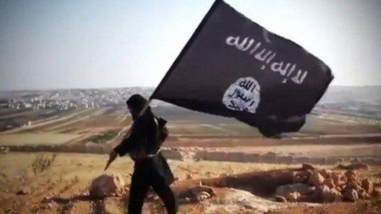 Un militant islamiste brandit un drapeau djihadiste quelque part en Irak (23-8-2013). Image tirée d'une vidéo postée sur Youtube. (AFP - Youtube)