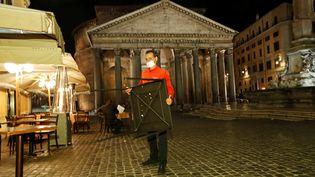Un restaurateur range une table de sa terrasse devant le Panthéon à Rome, le 23 octobre 2020, jour d'entrée en vigueur d'un couvre-feu local. (REMO CASILLI / REUTERS)