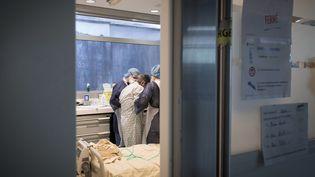 Des soignants prennent en charge un malade du Covid-19, le 27 avril 2020, à l'hôpital Lariboisière à Paris. (JOEL SAGET / AFP)