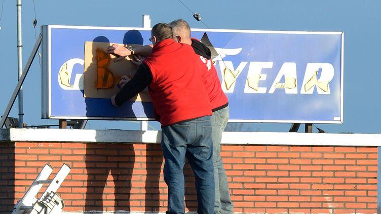 Des salariés de l'usine Goodyear d'Amiens-Nord transforment la pancarte du site, le 7 janvier 2014. (DENIS CHARLET / AFP)