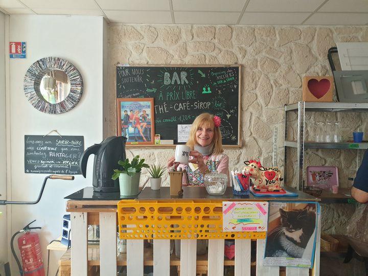Mireille, bénévole de la Boutique sans argent, derrière le bar à prix libre. Paris, le 11 août 2021 (LEELA BADRINATH)