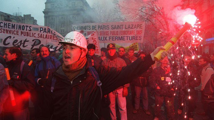 Un cheminot brandit un fumigène, lors d'une manifestation contre le plan Juppé, le 5 décembre 1995, à Paris. (PASCAL GUYOT / AFP)