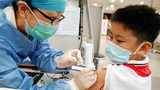 Un soignant vaccine un enfant, le 3 septembre 2021 à Shanghai (Chine). (LIU YING / XINHUA / AFP)