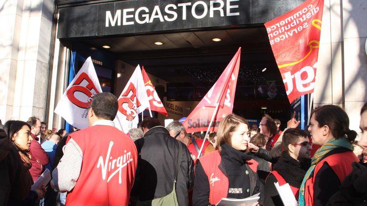 Des salariés et des représentants syndicaux manifestent devant le magasin Virgin Megastore des Champs-Elysées, à Paris, samedi 29 décembre 2012. (SEVGI / SIPA)