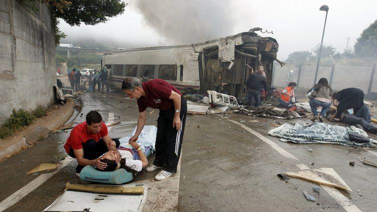 Deux hommes portent secours à une blessée après le déraillement du train au niveau de Saint-Jacques-de-Compostelle (Espagne), le 24 juillet 2013. (XOAN A. SOLER / LA VOZ DE GALICIA / AFP)