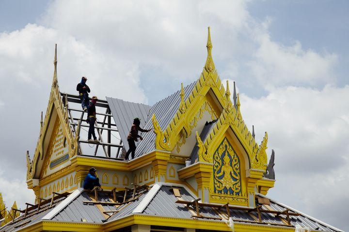 Des ouvriers finissent la toiture de l'un des monuments édifiés en l'honneur du roi défunt. (LIONEL DE CONINCK / FRANCE TELEVISIONS)