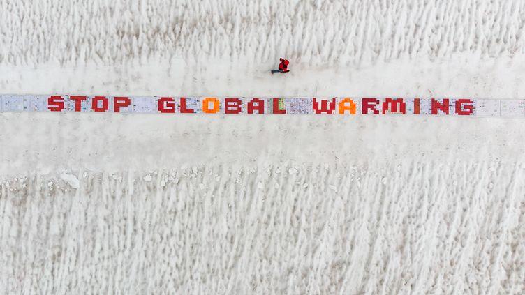 """Des écologistes déposent une bannière """"Stoppons le réchauffement climatique"""", le 13 août 2018 sur le glacier Aletsch (Suisse). (FABRICE COFFRINI / AFP)"""