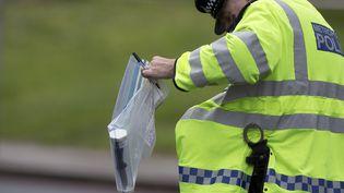 Un policier place un couteau sous scellés, jeudi 23 mai 2013,après le meurtre de Woolwich, à Londres (Royaume-Uni),dans lequel un soldat a été tué par deux extrémistes. (NEIL HALL / REUTERS)