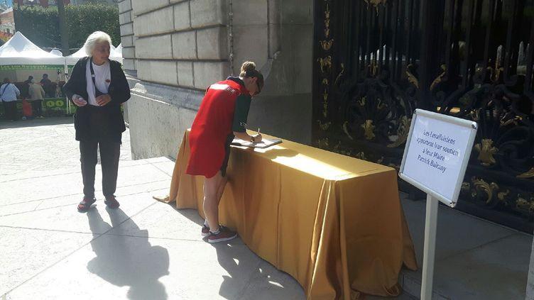 Une habitante de Levallois-Perret signe le Livre d'or en signe de soutien à Patrick Balkany, le 14 septembre 2019 (JEROME JADOT / FRANCEINFO / RADIO FRANCE)