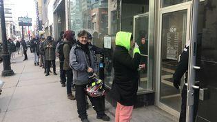 Des clients font la queue devantla boutique de la Société québécoise du cannabis (SQDC) de la rue Sainte-Catherine, principale artère commerciale de Montréal (Canada), le 18 mars 2020. (JACQUES LEMIEUX / AFP)