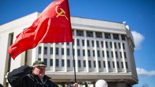 Un homme tient un drapeau soviétique devant le parlement de Crimée, à Simferopol, le 17 mars 2014. (HANNIBAL HANSCHKE / DPA / AFP)