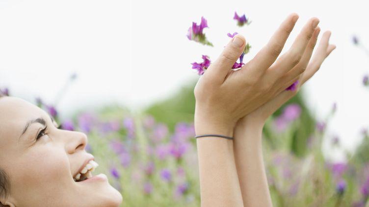 Une femme sourit en jetant des fleurs. Photo d'illustration. (LAURENCE MOUTON / MAXPPP)