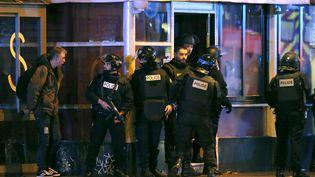 Les policiers situés à proximité de l'entrée du Bataclan se préparent à un assaut. (CHRISTIAN HARTMANN / REUTERS)