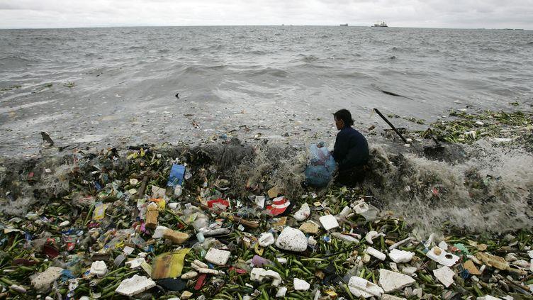 Un homme collecte des déchets ramenés par les vagues aux Philippines. (CHERYL RAVELO / REUTERS )