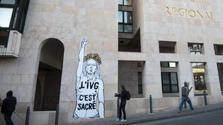 """Un passant s'arrête devantune œuvre du street-artist Emmanuel Mahn indiquant """"L'IVG, c'est sacré"""", à Marseille (Bouches-du-Rhône), le 8 mars 2017. (BERTRAND LANGLOIS / AFP)"""