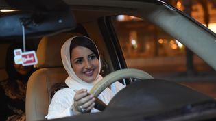Une Saoudienne au volant d'une voiture dans la capitale Riyad, peu après minuit, alors qu'une loi autorise les femmes à conduire à compter du dimanche 24 juin. (FAYEZ NURELDINE / AFP)
