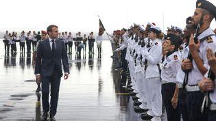 Emmanuel Macron passe les troupes en revue, à la descente de l'avion présidentiel, le 23 octobre 2019, à La Réunion. (RICHARD BOUHET / AFP)
