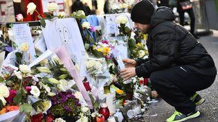 """Un homme se recueille en hommage aux victimes des attentats de Paris, devant le restaurant """"La Belle Equipe"""", le 22 novembre 2015 à Paris. (LOIC VENANCE / AFP)"""