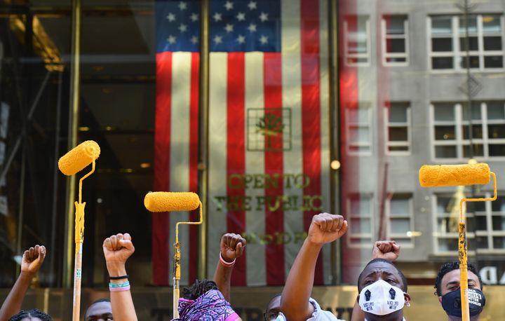 """Des militants lèvent leur poings et leurs rouleaux à peinture alors qu'ils peignent le slogan """"Black Lives Matter"""" (""""Les vies noires comptent"""") devant la tour Trump, le 9 juillet 2020 à New York. (ANGELA WEISS / AFP)"""