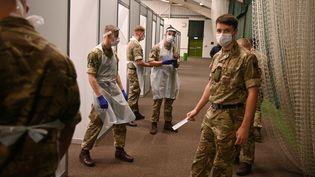Des soldats avec des équipements de protection se préparent à l'arrivée du public à l'intérieur du centre de dépistage du Covid-19àLiverpool, le 6 novembre 2020. (OLI SCARFF / AFP)