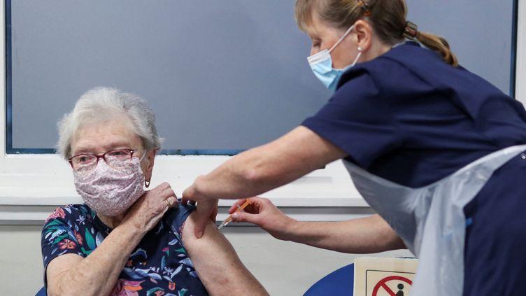 Une Britannique reçoit,en Écosse, une dose du vaccin contre le Covid-19 développé par AstraZenecaet Oxford, le 7 janvier 2021. Photo d'illustration. (RUSSELL CHEYNE / POOL / AFP)