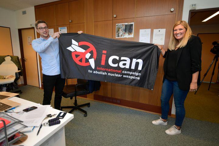 La dirigeante de l'Ican, Béatrice Fihn, et le coordinateur de l'organisation,Daniel Hogstan, brandissent une bannière de leur coalition, le 6 octobre 2017, à Genève (Suisse) pour fêter leur prix Nobel de la paix. (FABRICE COFFRINI / AFP)