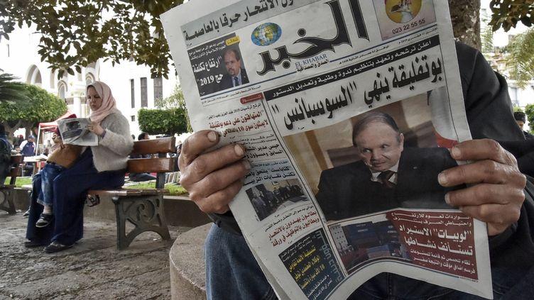 Un algérien lit dans un journal le 11 février 2019 un article sur l'élection présidentielle prévue pour le 18 avril.  (RYAD KRAMDI / AFP)