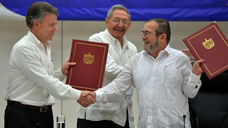 Poignée de main historique entre le président colombienJuan Manuel Santos (à g.) et le leader des Farc, Timoleon Jimenez (à dr.), le 23 juin 2016, à La Havane (Cuba). (ADALBERTO ROQUE / AFP)
