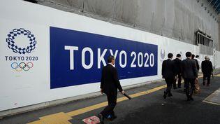 """Un panneau """"Tokyo 2020"""" devant un site de construction pour les Jeux olympiques, le 8 juin 2017. (KAZUHIRO NOGI / AFP)"""