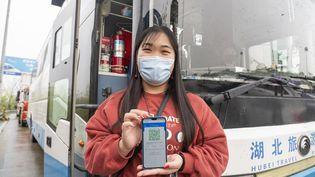 Une habitante de Wuhan (Chine)montre son code vert sur l'application Alipay Health Code, qui lui permet de se déplacer librement, le 24 mars 2020. (CAI YANG / XINHUA / AFP)