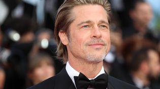 Le regard perdu de Brad Pitt face aux photographes des marches. (VALERY HACHE / AFP)