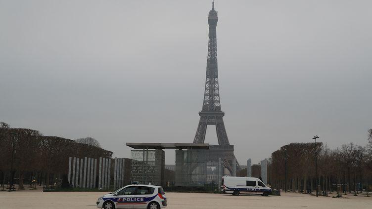 Une patrouille de police sur le Champ-de-Mars, près de la tour Eiffel à Paris, le 20 mars 2020. (LUDOVIC MARIN / AFP)