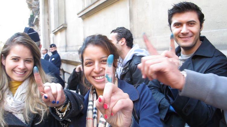 Des Tunisiens arborant leur doigt bleuté, signe qu'ils ont participé à l'élection de l'assemblée constituante de Tunisie, le 21 octobre 2011 à Paris. (FTVi)