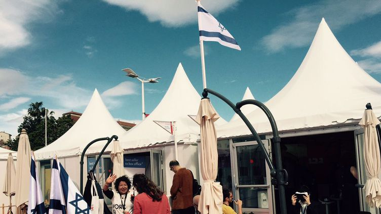 Le pavillon israélien au Festival de Cannes. Au premier plan, Eti Cohen, la directrice du département Films au ministère israélien de la Culture et du sport, fait un signe de la main à des visiteurs qui arrivent sur le stand le jeudi 12 mai 2016. (DR)
