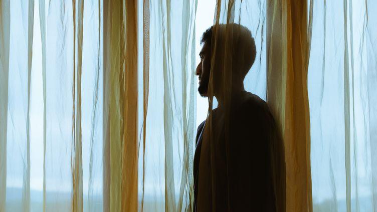Un homme regarde par sa fenêtre pendant la deuxième période de confinement contre le Covid-19, le 3 novembre 2020, à Cassagne (Haute-Garonne). (LILIAN CAZABET / HANS LUCAS / AFP)