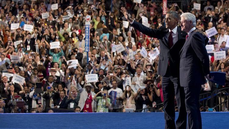 Bill Clintonrejoint par le président américain Barack Obama, à la fin de son discours devantla convention démocrate, le 5 septembre 2012 à Charlotte (Caroline du Nord). (SAUL LOEB / AFP)