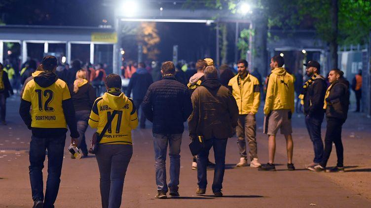 Des fans du Borussia Dortmund quittent le stade après le report du quart de finale aller de la Ligue des champions contre Monaco, le 11 avril 2017. (FEDERICO GAMBARINI / AFP)