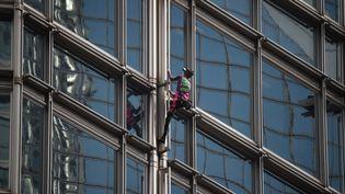 Alain Robert escaladant la façade d'un gratte-ciel à Hong Kong, le 16 août 2019. (LILLIAN SUWANRUMPHA / AFP)