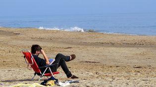 Un homme profite du soleil sur laplage catalane de Tarragone, en Espagne, le 25 décembre. (JAUME SELLART / SIPA)