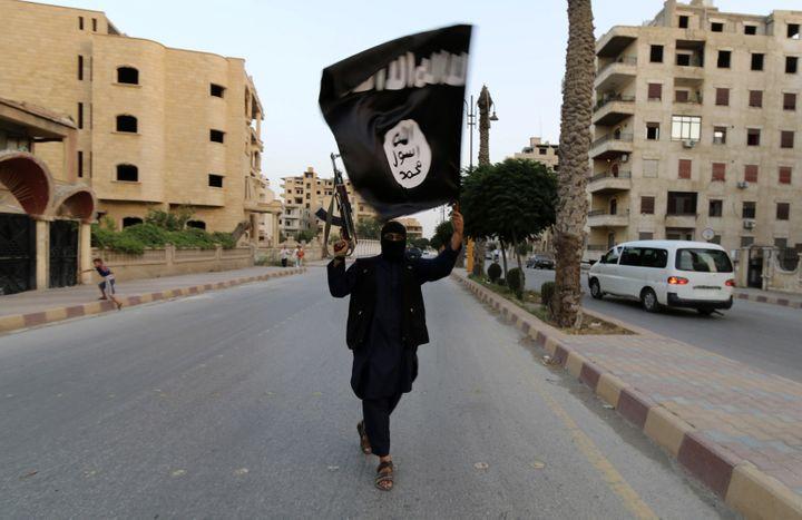 Un homme agite un drapeau de l'organisation Etat islamique dans les rues de Raqqa (Syrie), le 29 juin 2014. (REUTERS)