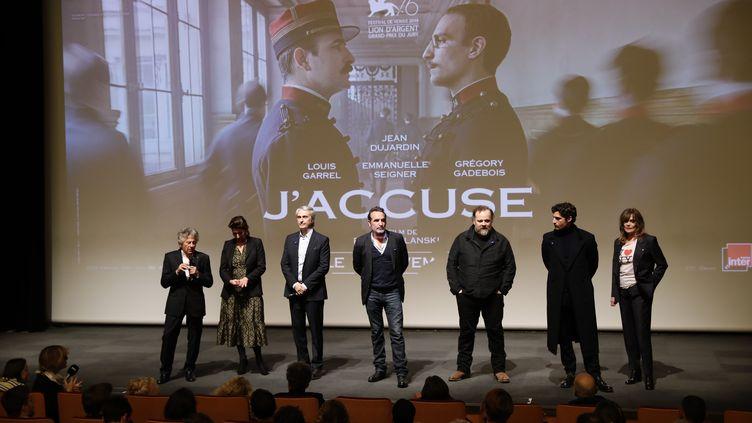 """Une partie de l'équipe du film """"J'accuse"""" de Roman Polanski le 4 novembre 2019 lors d'une avant-première du film à Paris. De gauche à droite :Roman Polanski, Sidonie Seydoux (Gaumont), le producteur Alain Goldman, l'acteur Jean Dujardin, l'acteur Gregory Gadebois, l'acteur Louis Garrel et l'actrice Emmanuelle Seigner. (THOMAS SAMSON / AFP)"""