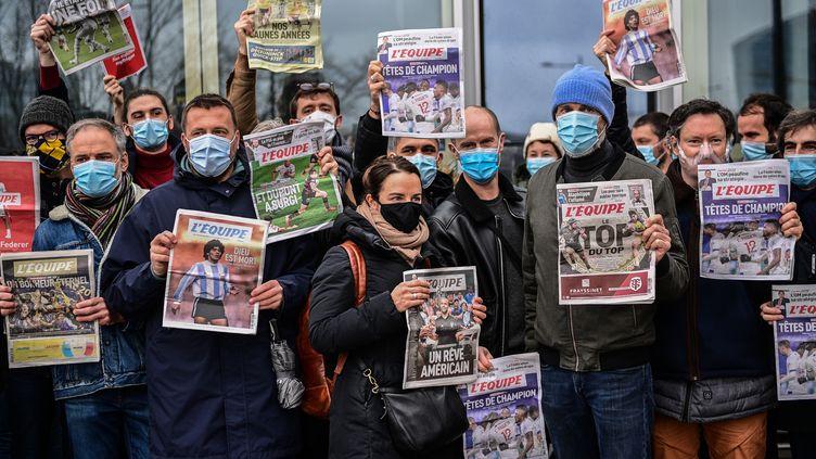 """Rassemblésdevant le siège social à Boulogne-Billancourt, des salariés grévistes du journal """"L'Équipe"""" posent avec des unes du quotidien, le 13 janvier 2021. (MARTIN BUREAU / AFP)"""