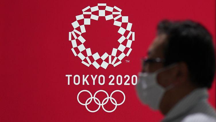 Un passant devant une ancienne affiche des JO, ceux-ci étant déjà reprogrammés pour l'année suivante, le 15 juin 2020, à Tokyo. (KIMIMASA MAYAMA / EPA)