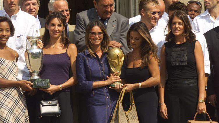 Les épouses de Zinedine Zidane et d'Emmanuel Petit tiennent la Coupe d'Europe et la Coupe du monde, lors d'une réception à l'Elysée, le 31 août 2000. (JACQUES DEMARTHON / AFP)
