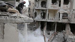 Un homme dans des décombres, dans la Ghouta orientale, dans la banlieue de Damas, la capitale syrienne, le 22 février 2018. (ABDULMONAM EASSA / AFP)