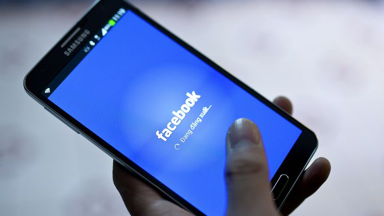 Un smartphone avec l'application Facebook.  (LUONG THAI LINH / EPA)