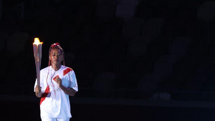 Naomi Osaka s'avance pour allumer la vasque olympique dans le stade olympique de Tokyo lors de la cérémonie d'ouverture, le 23 juillet. (TAKUMI HARADA / YOMIURI)