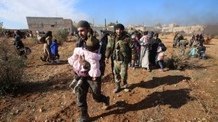 Les résidents syriens fuyant la violence se rassemblent dans le village d'Aziza, dans la banlieue sud-ouest de la ville d'Alep, au nord de la Syrie, le 8 décembre 2016. (YOUSSEF KARWASHAN / AFP)